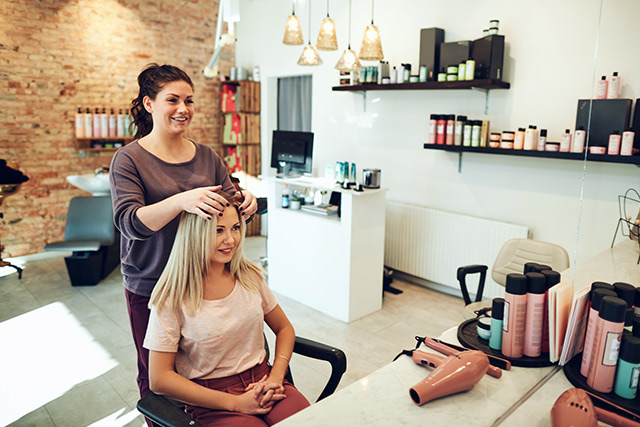 Woman working in cosmetology salon with customer