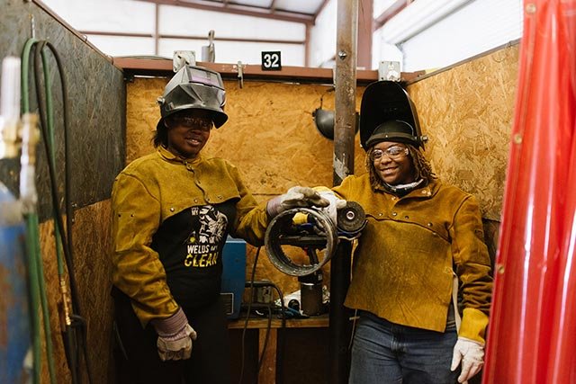 Two Compass Career College Pipe Technician student women in class.