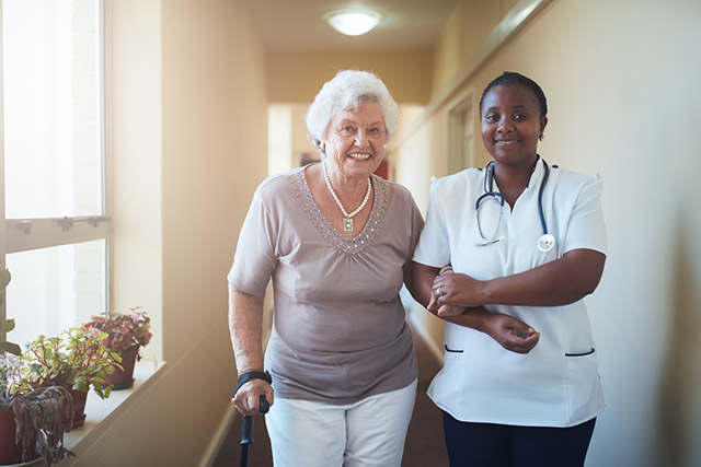 A certified nursing assistant (CNA) helping a patient.