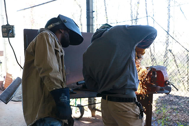 Compass Career College Pipe Technician instructor watching a student weld